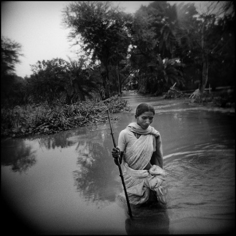 Woman wades water in 2008 during the Kosi floods in Bihar, India.