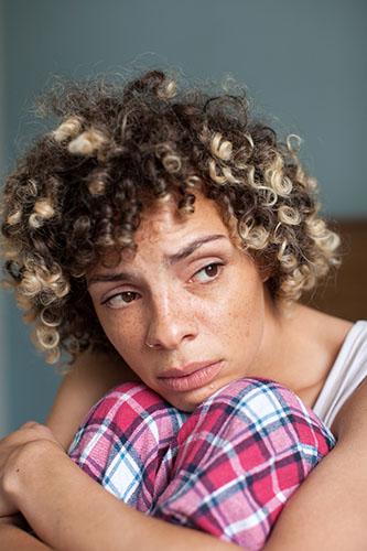 Image of woman in pyjamas hugging her knees
