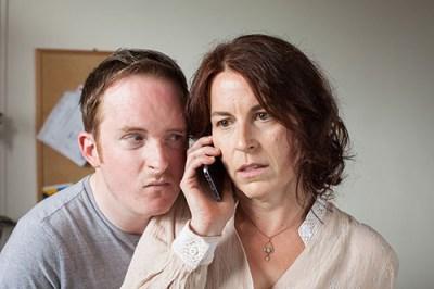 Photograph of man listening on on woman's phone conversation.