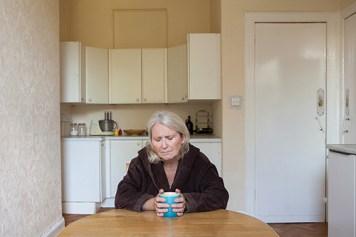 Photograph of woman at kitchen table clutching mug looking sad.