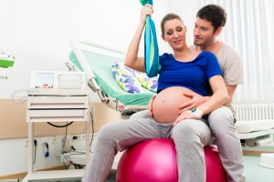 pregnant woman on ball in hospital room with husband