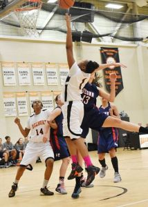 Taj Lewis scores as Breonna Pinkcett boxes out. Photo by Phuong Tang, RCC Marketing Department.