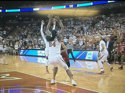 NC State's Dominique Wilson runs into Texas' Joyner Holmes with eight seconds left, which resulted in a controversial charging call. ESPN photo.