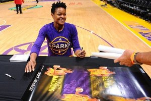 Alana Beard signs items after a game. Photo by NBAE via Getty Images.