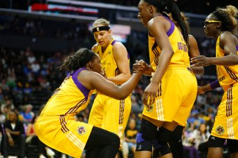 Sparks members help up teammate Chelsea Gray. Photo by Maria Noble/WomensHoopsWorld.