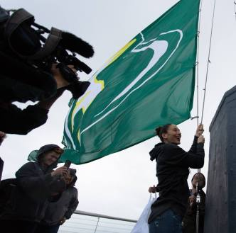 Sue Bird helps raise the flag to the top. Neil Enns/Storm Photos.