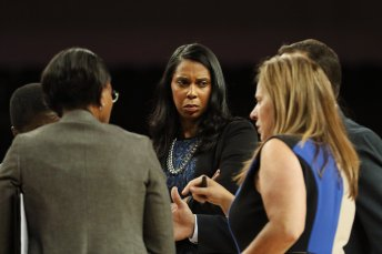 UCLA coaches confer at a timeout. Maria Noble/WomensHoopsWorld.