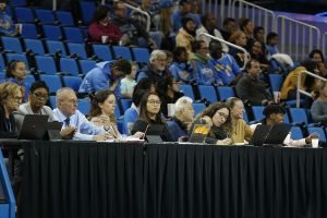 Sue Favor, in the gold shirt, has a laugh with her assistant at a game at Pauley Pavilion in December, 2019. Maria Noble/WomensHoopsWorld.
