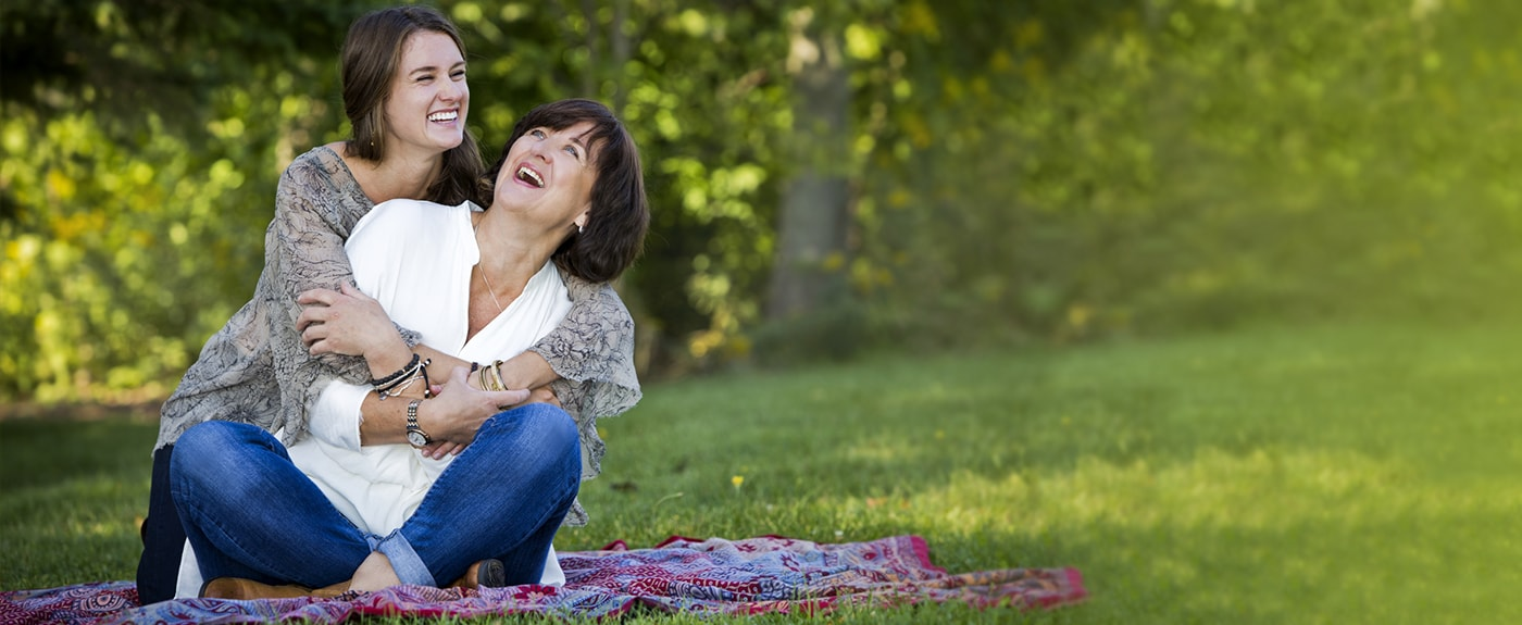 Mother and adult daughter laughing in the park