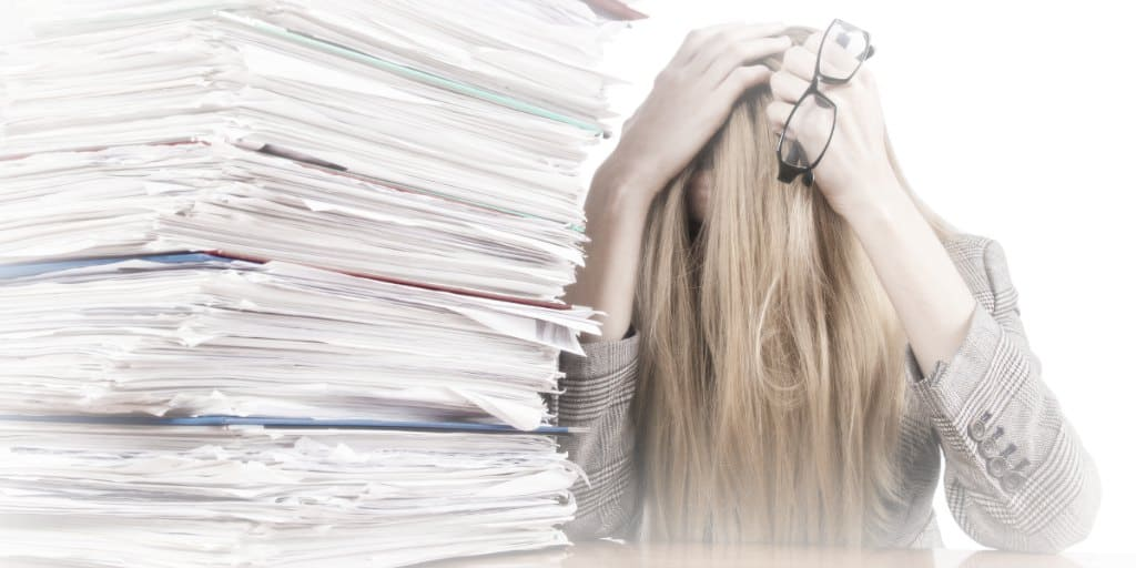 large stack of documents, women holding her head in stress