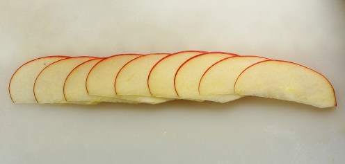 Pro Tip: For the most success with your apple roses, place each apple slice so that it lays halfway over the previous slice (lots of overlap gives the rose structural stability). If your slices are thinner at one end, place the thin end to the outside of the overlap (this will make rolling easier).