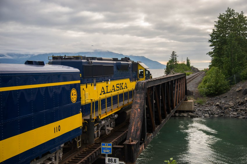 The blue and yellow Alaska railroad train is captured as is crosses an old steel bridge over Bird creek near the turnagain arm. The words Alaska are clearly seen on the side of the train. Mountains and tees are seen in the background.