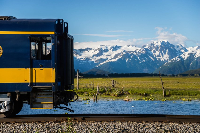 A blue and yellow railroad train crosses a beautiful summer scene over an Alaskan Wetland. The wetland is covered in vibrant green grass. There are snow capped mountains in the background over a blue sky.