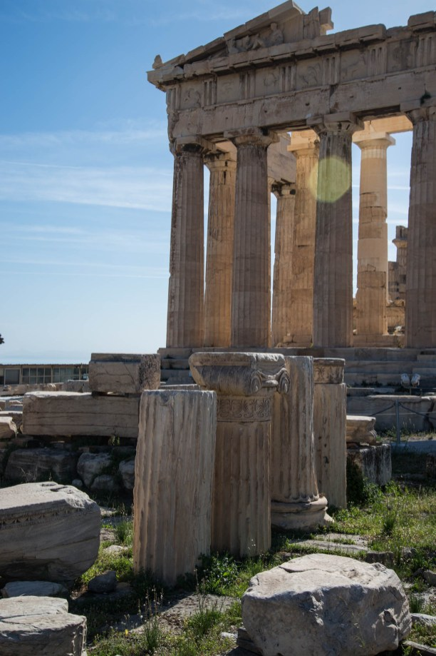 The ruins of ancient greece's parthenon are seen in Athens on a sunny day. A few Marble pillars have fallen and sit in a grass field in front of the parthenon.