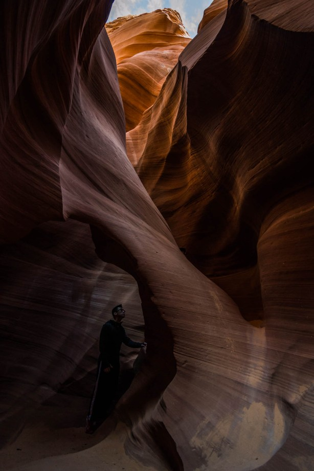 A man stands under a standstone arch formation in a slot canyon.