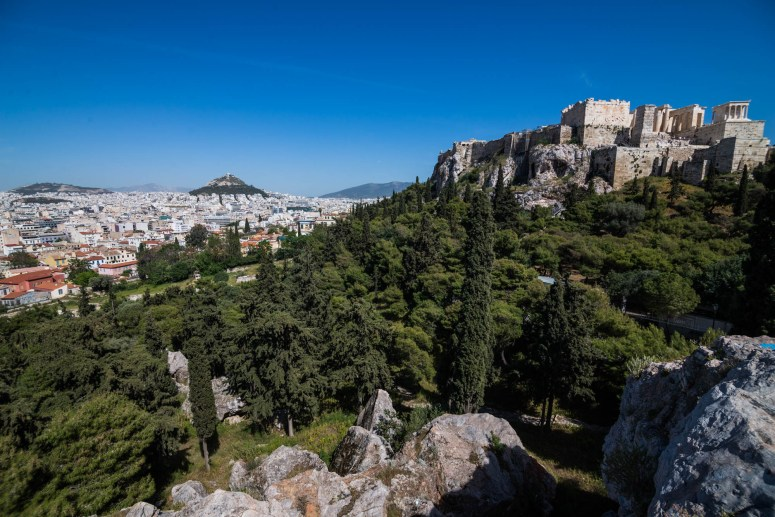 The ancient Acropolis and the city of athens is seen from Aeropagus hill. Mount Lycabettus is seen in the distance.