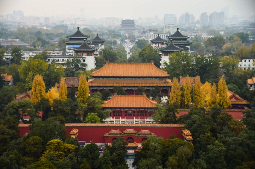 The forbidden palace in beijing china is seen from a vantage point during autumn. A think smog blurs the rest of the city.