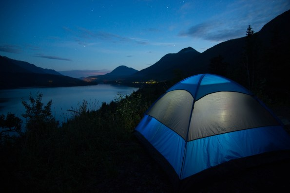 A blue and grey tent is illuminated from the inside as it sits above the large Kenai lake in Cooper Landing, Alaska. It appears to be twilight but it is already past midnight in Alaska's summer.