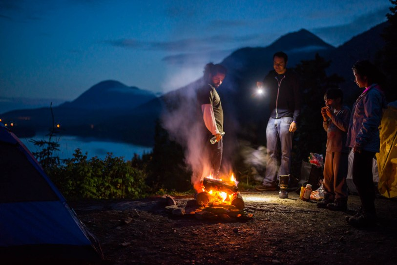 A group of friends enjoy vegan hotdogs and a campfire during twilight. The sparsely spaced lights of Sterling can be seen among mountains and Kenai Lake.