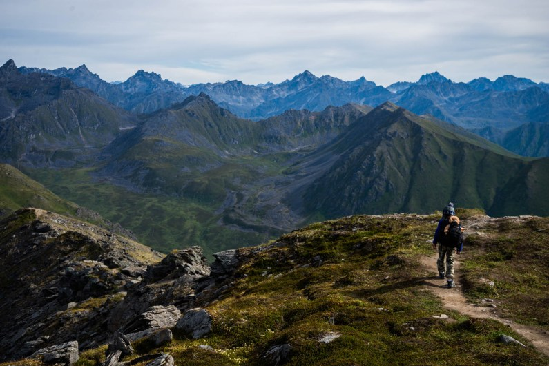 A young boy with a cute beanie is hiking down an amazing trail while carrying a large backpack and his favorite stuffed animal, a monkey named coco. Ahead of him are the large jagged mountains of Hatcher's Pass.