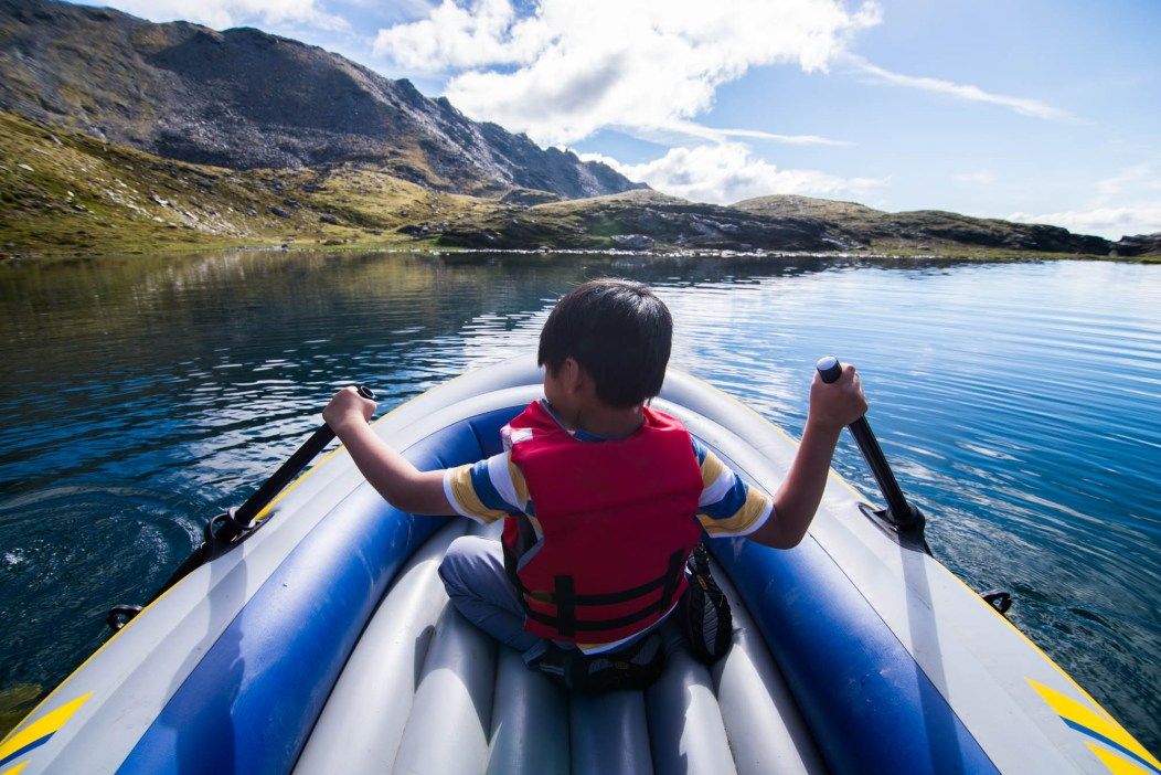 A young boy in a red life jacket seen from behind paddles an inflatable raft on a small alpine lake on top of a mountain. The area is called april bowl in Hatchers Pass, Alaska.
