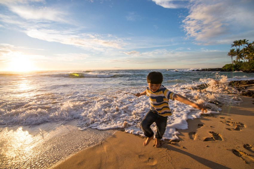 A playful young boy is playing at a secluded beach in hawaii. The sun is setting with palm trees in the background and the boy is running away from the wave before they catch him.