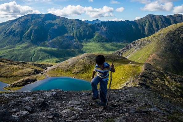 young boy with a walking stick climbs a remote mountain in Hatchers pass alaska. Seen behind him is a long trail, pristine alpine lake and large green mountains.