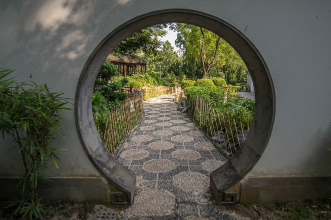 A circular passage in a stone wall shows a garden pathway in Hong Kong's Kowloon walled City Park
