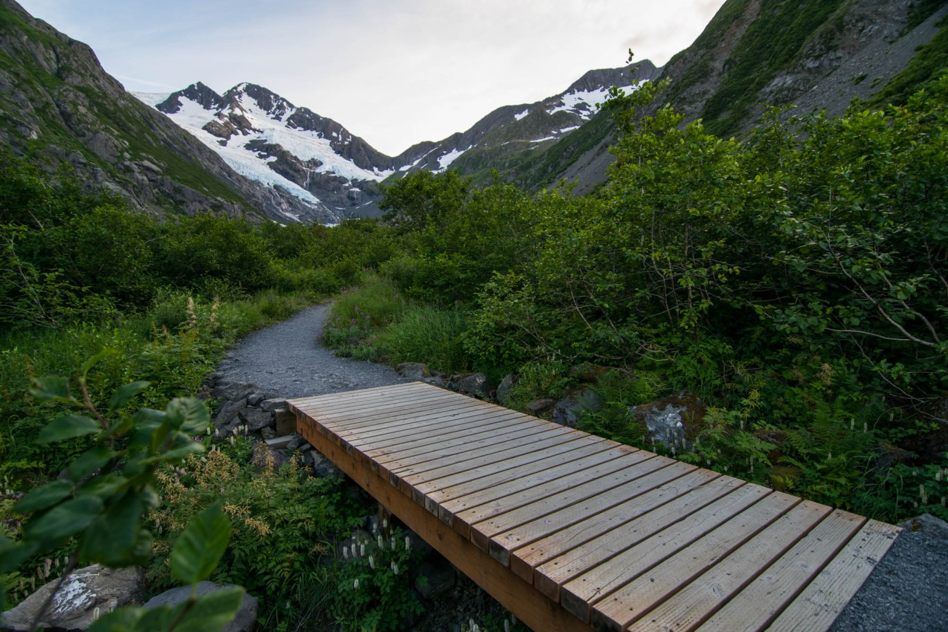 A small wooden foot bridge crosses a creek along a path through green bushes towards a mountain glacier known as Byron glacier.