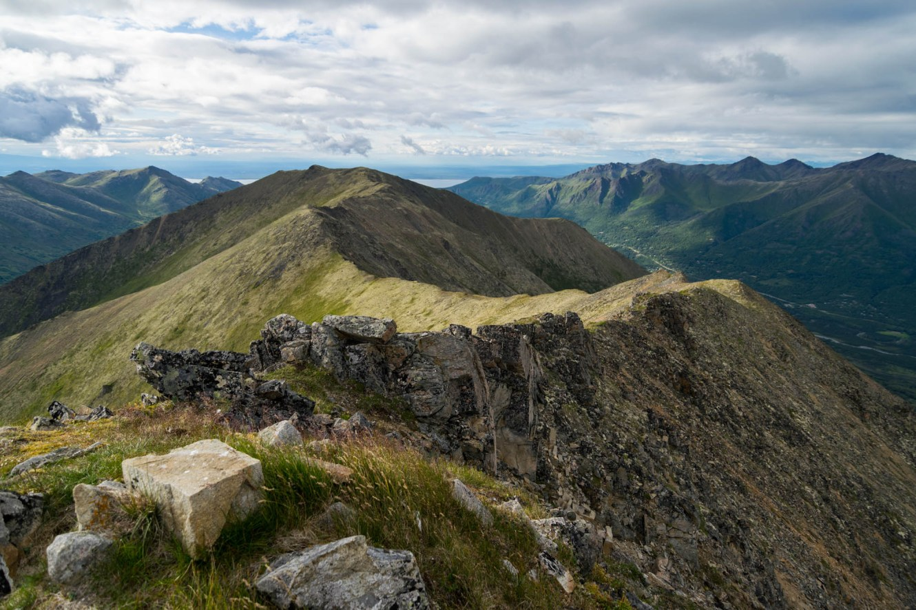 A winding mountain ridgeline accessible from Harp Mountain makes its way over the town of Eagle River, Alaska. Short grass, lichens and other apline plants are seen among the stones on the mountain top.