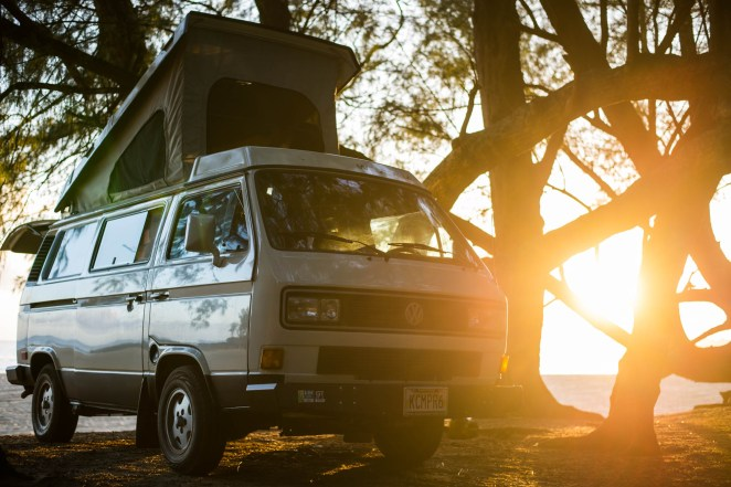 A volkswagen westfalia camper van bus is seen parked on a forested beach with its roof tent extended as the sun shines through trees.
