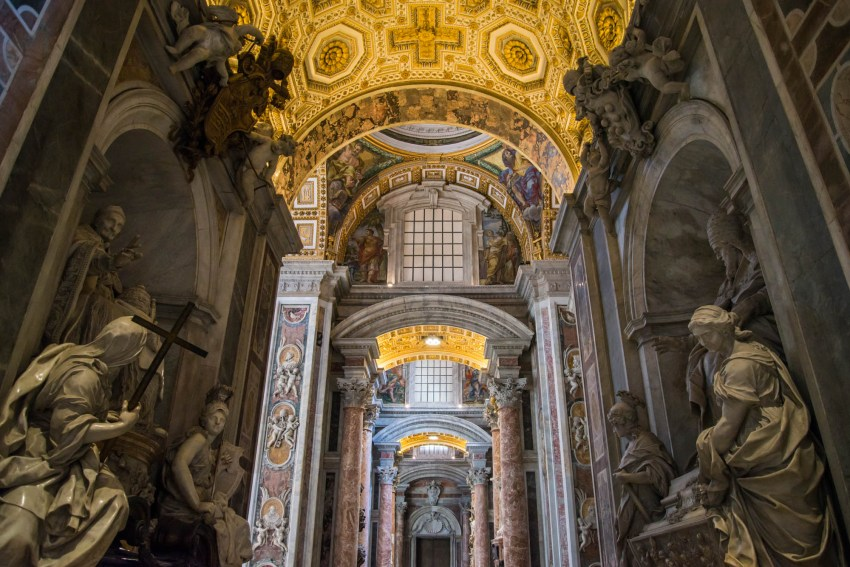 Marble Statues line a delicately detailed hallway in St. Peter's Bascilica. Red marble pillars hold up golden ceilings. The collection of staues emanates a feeling of greatness and heroism.
