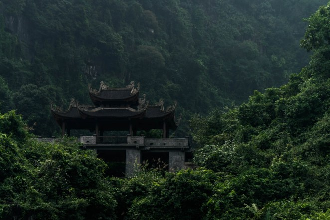 A buddhist temple fashioned in traditional chinese architecture is perched high in the mountains in a thick impassable jungle. Seen from Trang An Vietnam.