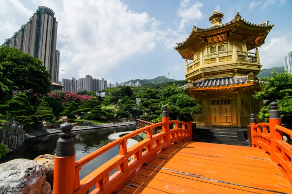 A red wooden bridge leads to a golden temple in Hong Kongs Nan Lian Garden. The Garden contrasts with the skyscrapers in the background