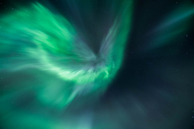 Strong streaks of electric green and subtle purple Northern lights burst directly overhead. Many stars are seen overhead.