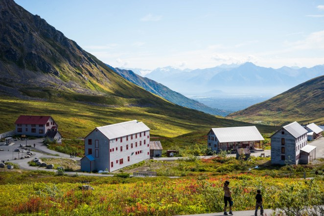 A young mother and her child take a stroll on a bright summer day high in the mountains of hatcher's pass. The flora is bright green and buildings from an old abandoned gold mine are seen below.