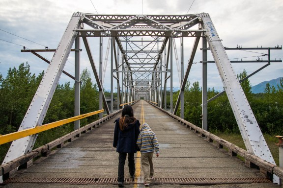 A mother guides her young child on an abandoned steel framed bridge over the Knik River in Alaska.