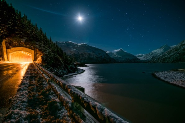 A full moon illuminates a winter scene over Portage Lake in Alaska. The view is seen from the edge of a road bridge that overlooks the lake. The road continues into a brightly lit mountain tunnel.
