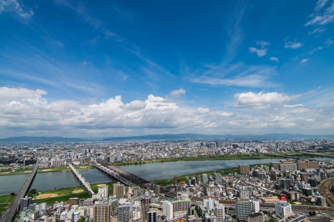 The mega-metropolis of Osaka japan and the yodo river are seen from above on a bright sunny day.