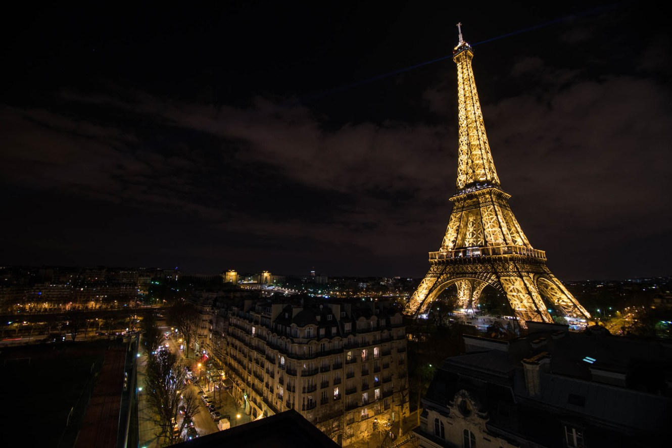 Paris streets are seen from a rooftop at night. The Eiffel tower is seen just a block away