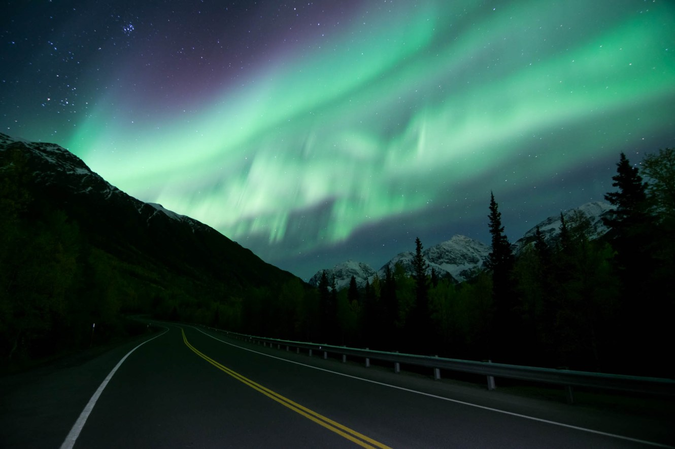 Sublte purple and bright green northern lights burst over a forest road in alaska. Headlights illuminate the road slightly. Stars shine overhead.