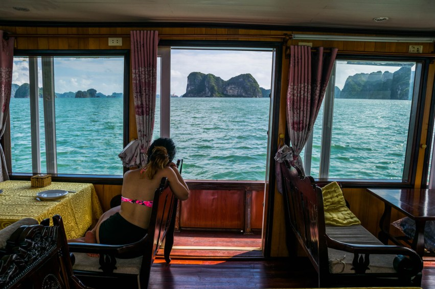 A young woman relaxes aboard an empty cruise ship as she peers out a window towards Vietnam's Halong Bay.