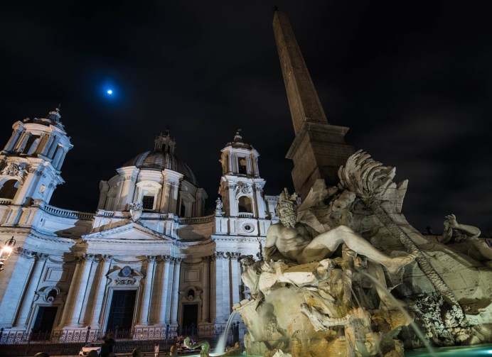 An old roman water fountain known as the fountain of the four rivers is seen with its egyptian obelisk on a moonlit night.