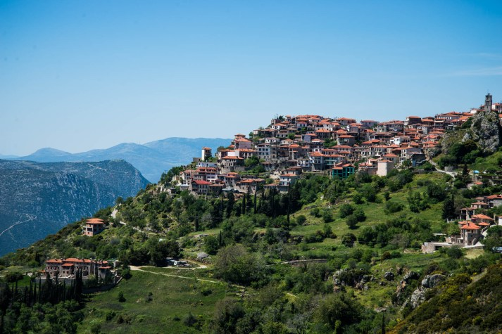 Arachova, a small greek town is seen on a mountain top surrounded by green grass, shrubs and trees.