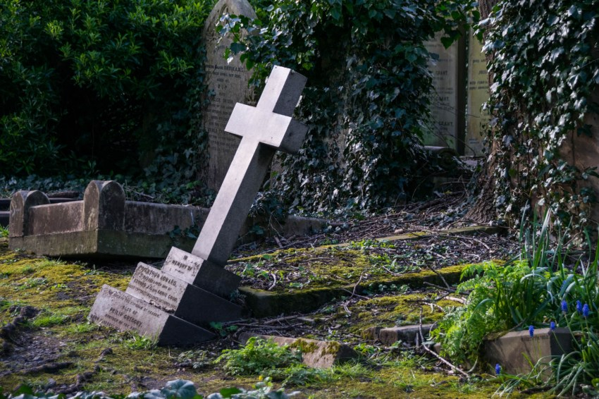 A christian cross tombstone is slowly sinking into its grave. Its surrounded by other old tombstones in London's Highgate cemetery.