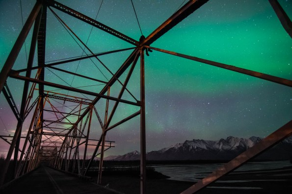 Person climbed on top of an abandoned bridge in alaska to view the northern lights