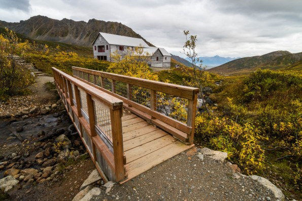 A small wooden bridge crosses a small creek in Hatcher's pass' Independence gold mine. Its a cloudy alpine mountain scene during fall.