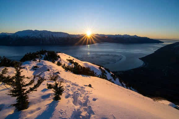 A starburst sunset is seen over the snowcapped mountains surrounding the Turnagain arm. The Birdridge trail looking back is covered in deep snow.