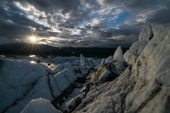 A starburst sunset is seen from the jagged ice of Matanuska glacier