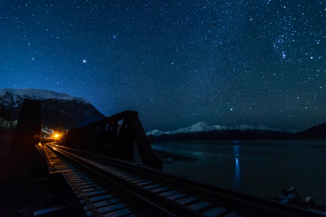 Thousands of stars are seen over the ocean and over the Alaska railroad bird creek bridge. A light is seen over the railroad tracks as if it were the headlight of an oncoming train.